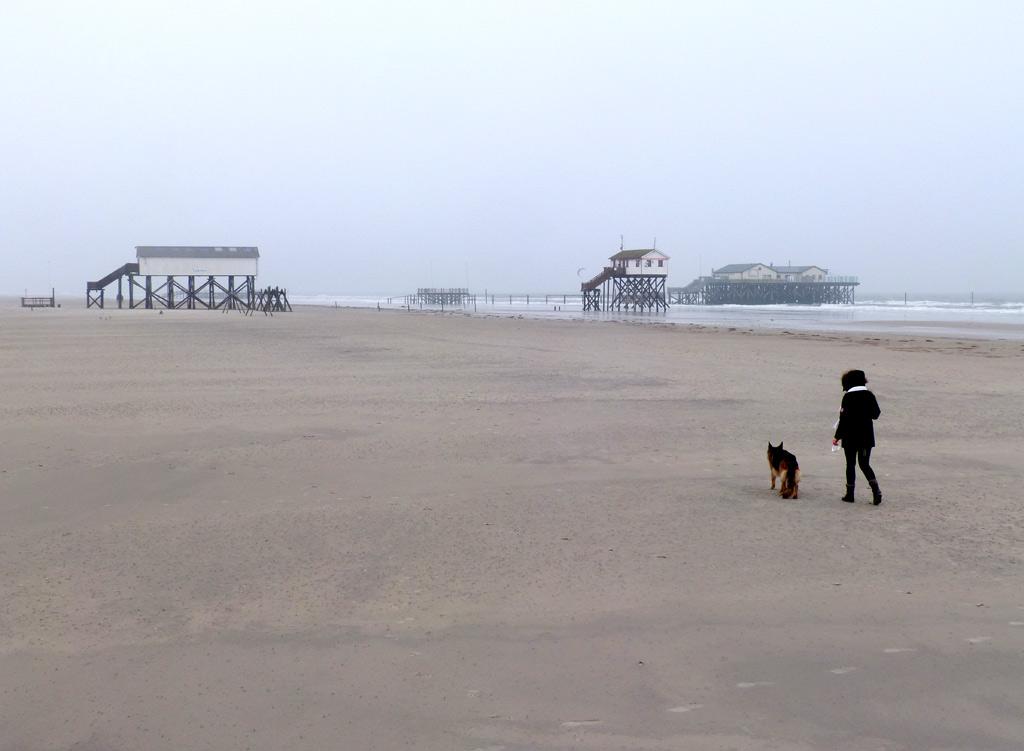 Mädel mit Hund am Strand von St. Peter-Ording