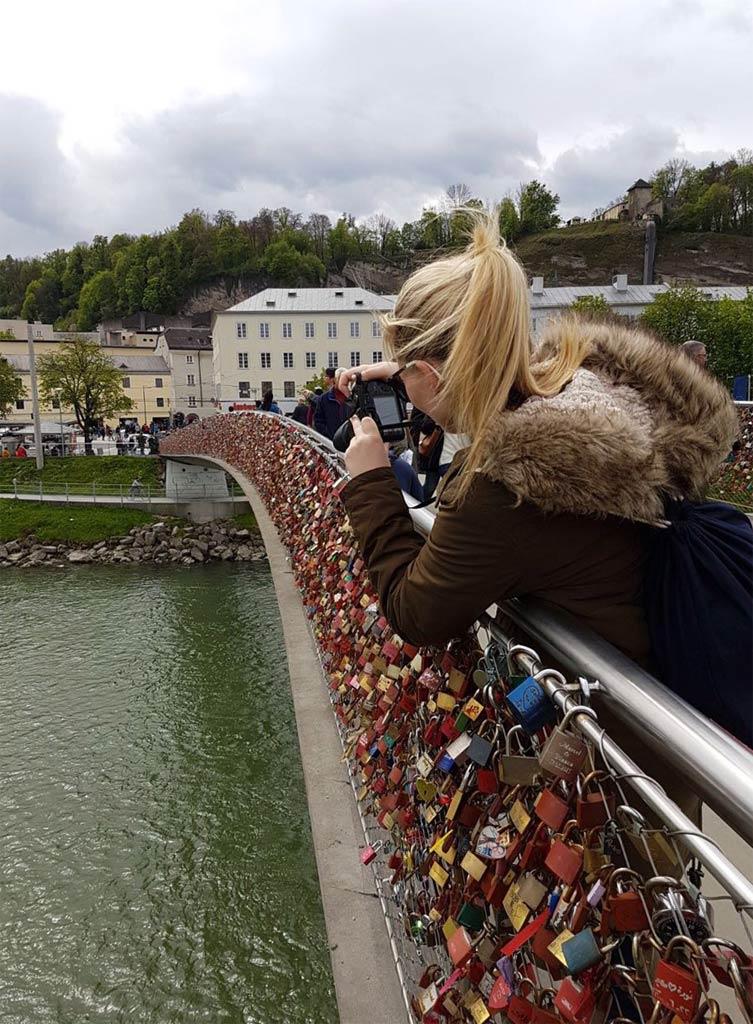 Frau fotografiert Liebesschlösser Brücke in Salzburg
