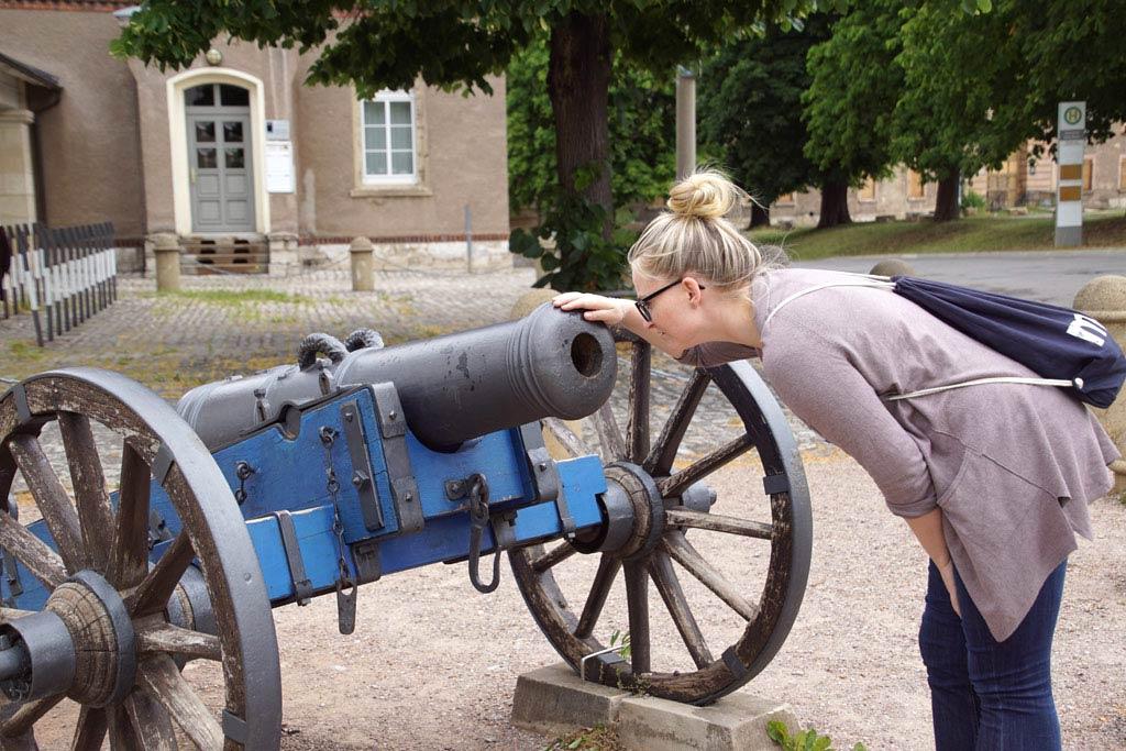 Frau guckt in Kanonenrohr