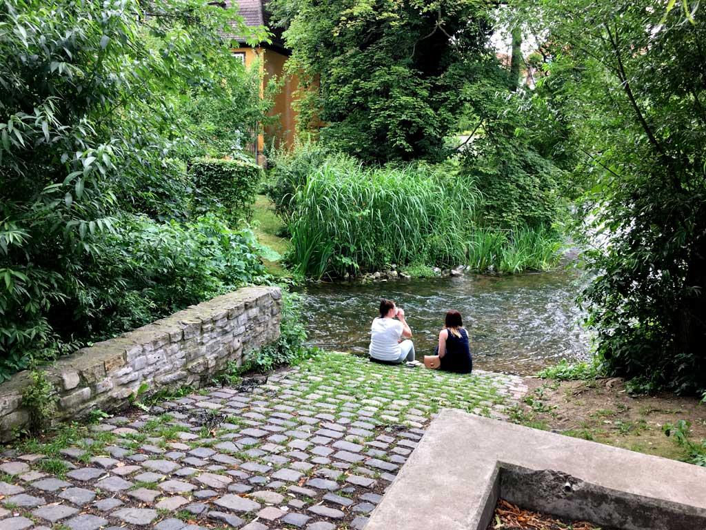 Frauen sitzen Bach Park Erfurt