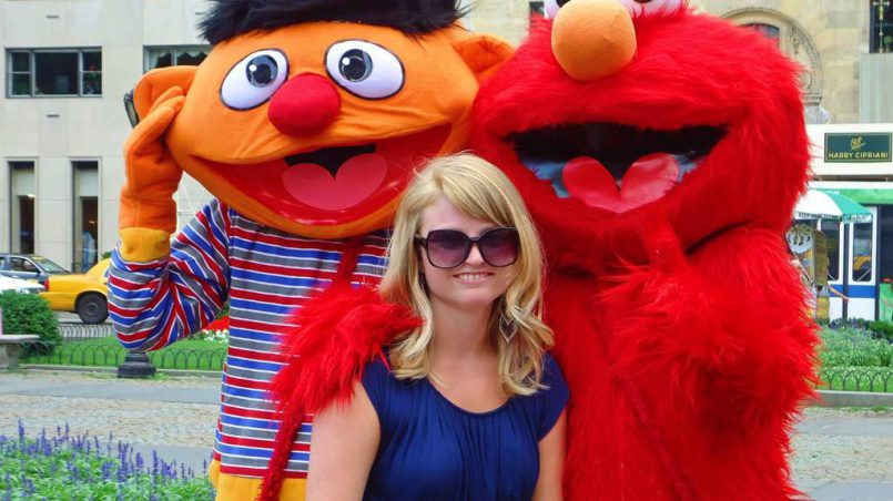 Girl standing in front of Ernie and the Grobie of Sesame Street