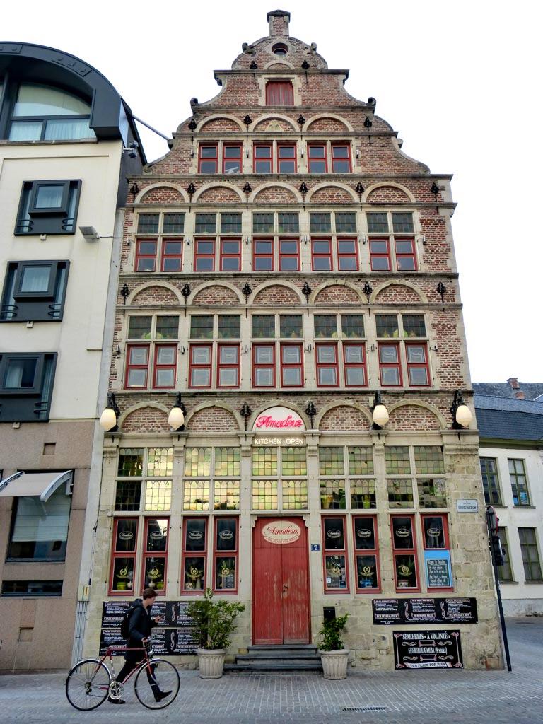 Fachwerkhaus mit roter Tür in Gent mit vorbeilaufendem Fahrradfahrer, Gent Sehenswürdigkeiten, Moments of Travel